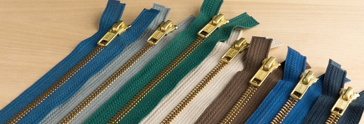 Brass Jacket Zippers on Wooden Work Table in Different Colors
